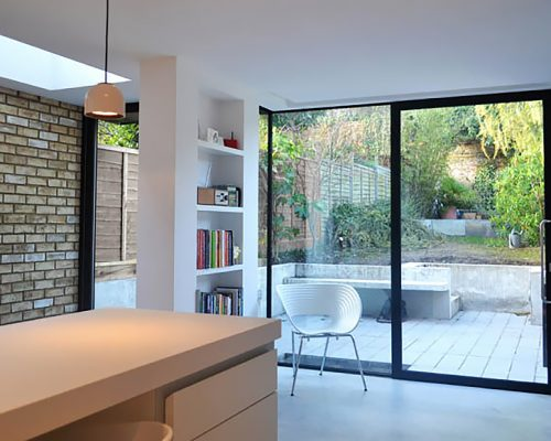 Kitchen and dining area that leads to the garden, with natural light provided by a skylight