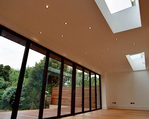 Two skylights above an extension with a wooden floor and end to end glazed doors