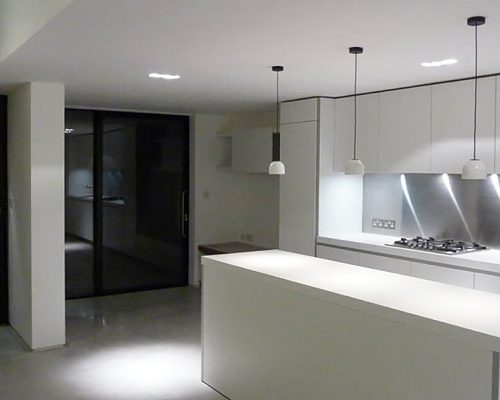 Kitchen at night lit by spot lamps